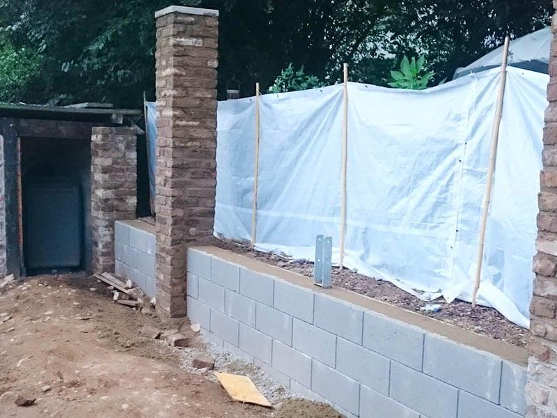 Pfosten aus Feldbrandstein, Mauer aus Betonsteinen
