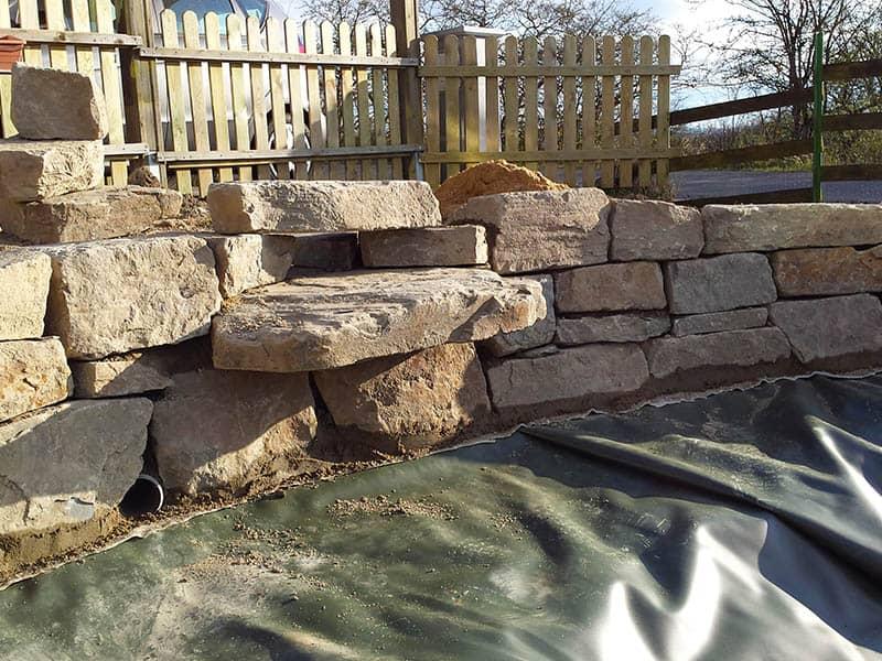 Grauwacke Natursteinmauer im Gartenteich