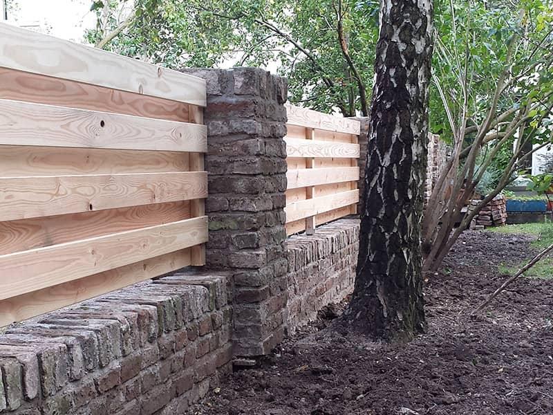 Mauer aus Feldbrandstein und Holzelemente aus Sibirischer Lärche